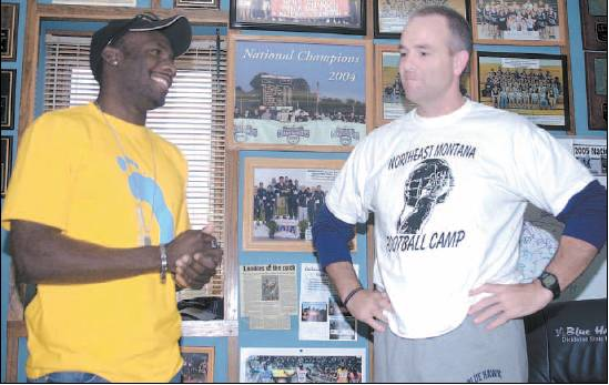 Derrick Atkins, left, and Dickinson State track and field coach Pete Stanton speak in Stanton's office at the DSU athletic department. Photos of the Blue Hawks' national track and field championships, along with photos of Atkins' recent accomplishments, adorn Stanton's wall.